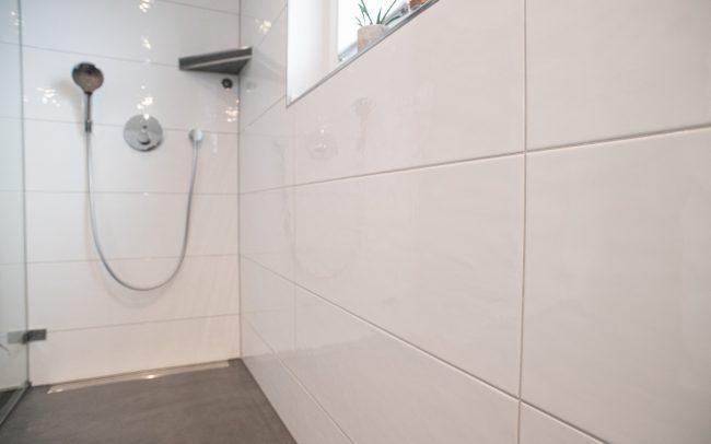 Große Wandfliesen im Bad, weiß glänzend