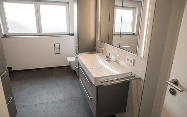 Großes Badezimmer mit eleganten Möbeln und großen Fliesen